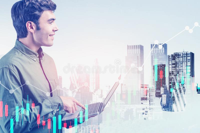 Smiling trader with laptop in city, forex graph royalty free stock photo