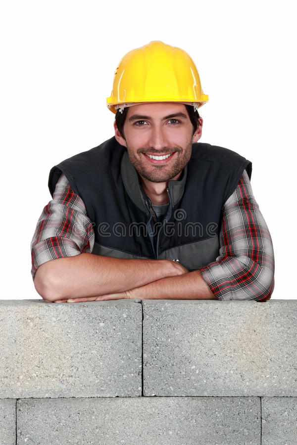 Smiling tradesman. Leaning on a stone wall royalty free stock image