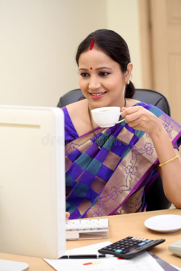 Smiling traditional woman drinking coffee at her desk royalty free stock images