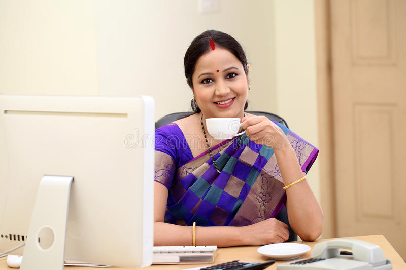 Smiling traditional woman drinking coffee at her desk royalty free stock image