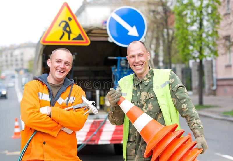 Smiling traffic sign marking technician workers. On city street during road surface painting works stock image