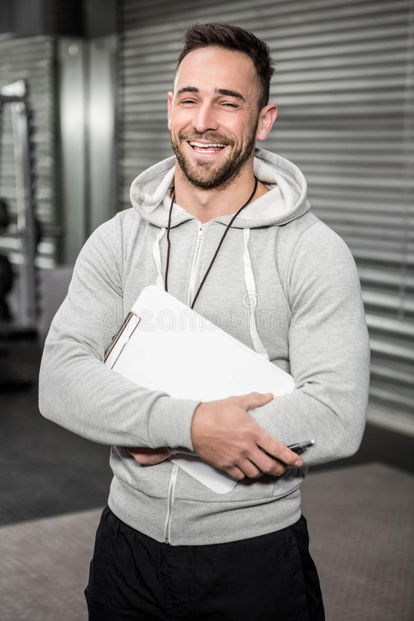 Smiling trainer holding clipboard stock images