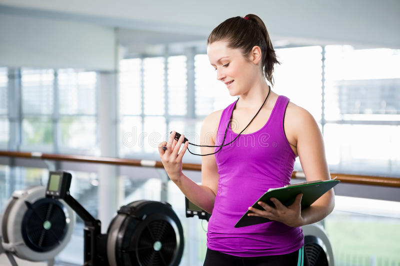 Smiling trainer looking at stopwatch stock photography