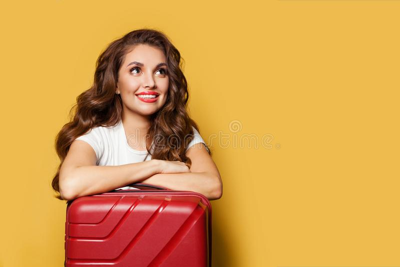 Smiling traveler tourist woman with red suitcase traveling abroad to travel on weekends getaway, air journey concept royalty free stock photography