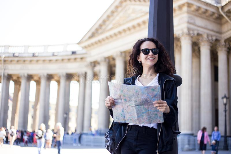Smiling traveler woman wearing backpack and black sunglasses hold location map in hands, near cathedral background. royalty free stock photography