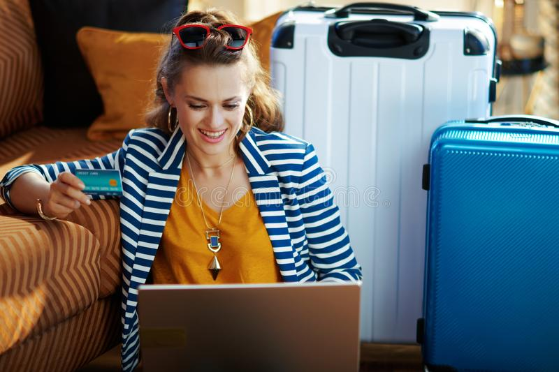 Smiling trendy woman with credit card booking tickets on laptop. Smiling trendy woman in striped jacket with credit card booking flights online on a laptop while royalty free stock images