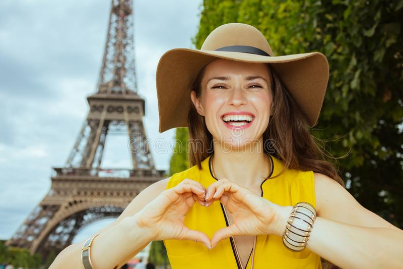 Smiling trendy woman showing heart shaped hands. Smiling trendy woman in yellow blouse and hat at Champ de Mars overlooking Eiffel tower in Paris, France showing stock photography