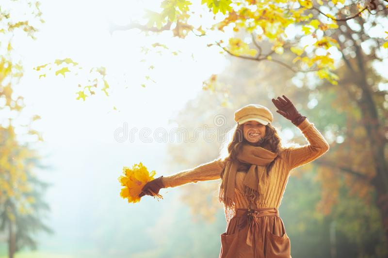 Smiling trendy woman with yellow leaves outdoors in autumn park royalty free stock photos