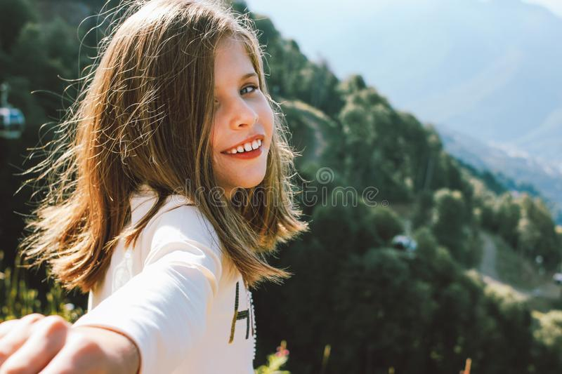 Smiling tween girl reaches out to camera follow me on background of beautiful mountains, family travel concept royalty free stock images