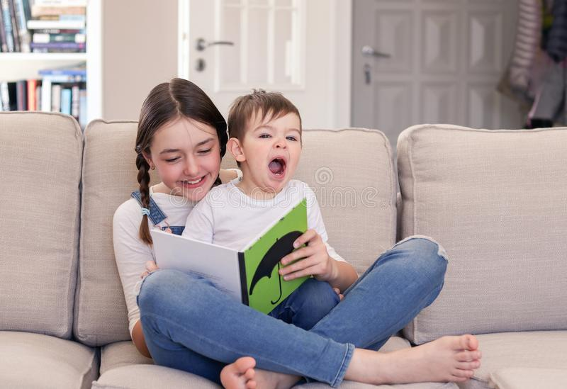 Smiling tween girl reading book to her cute little brother sitting on her lap and yawning on sofa at home. Siblings care and love. stock photos