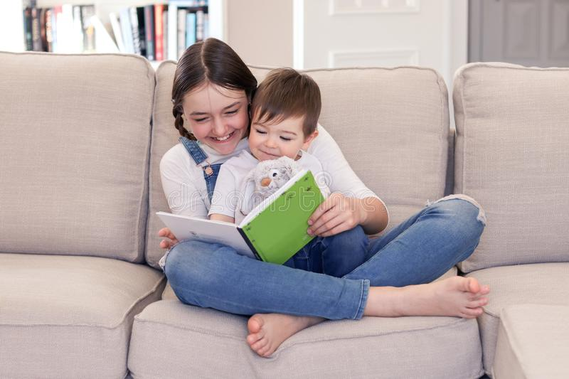 Smiling tween girl reading book to her little brother sitting in her arms with soft furry rabbit toy on sofa at home. stock photo