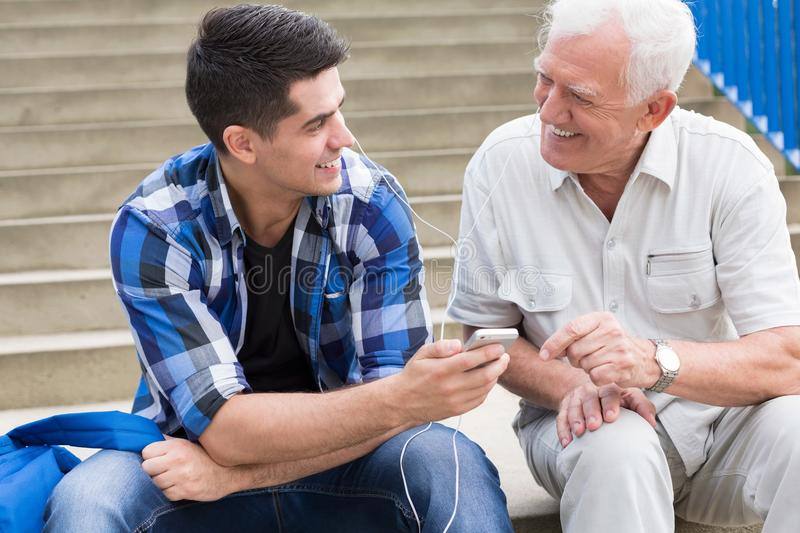 Smiling two men. Smiling young men talking with his grandfather royalty free stock image