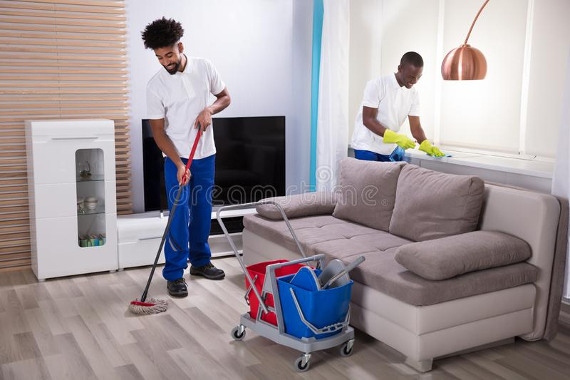 Smiling Two Young Male Janitor Cleaning The Living Room stock image
