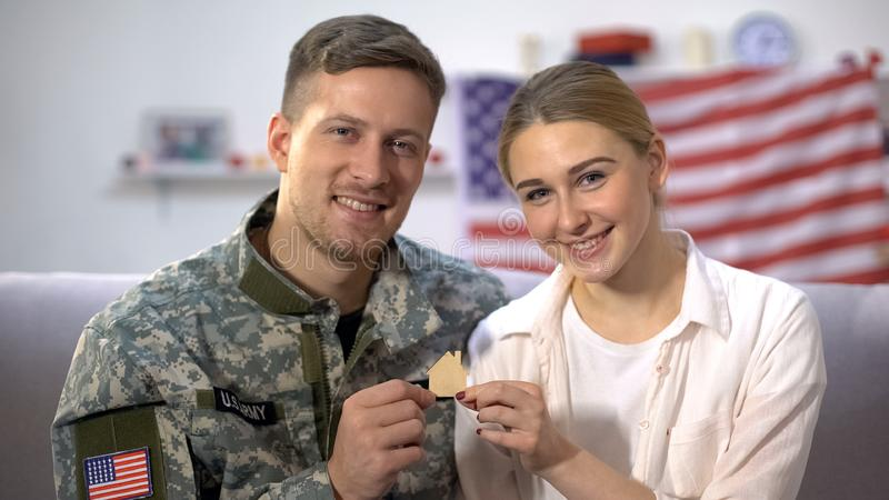 Smiling US male soldier and his wife showing wooden house sign on camera, family. Stock photo royalty free stock images