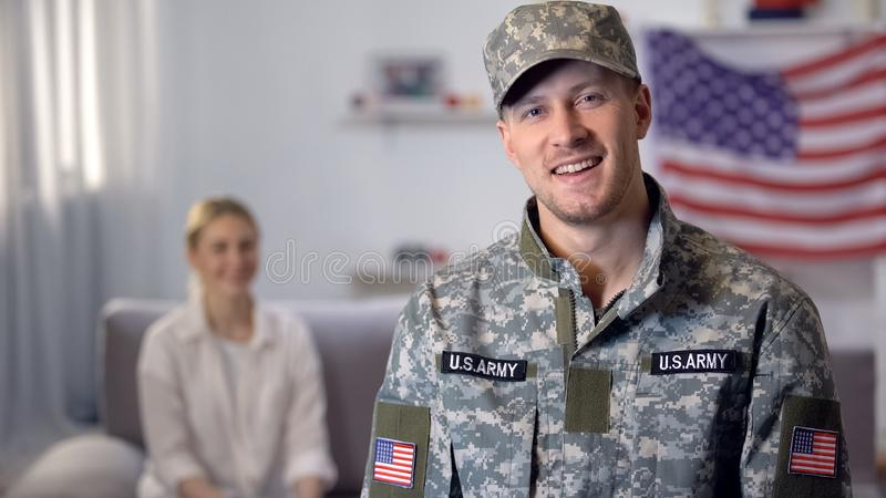 Smiling US military man looking at camera, wife sitting on background, support. Smiling US military men looking at camera, wife sitting on background, support royalty free stock image