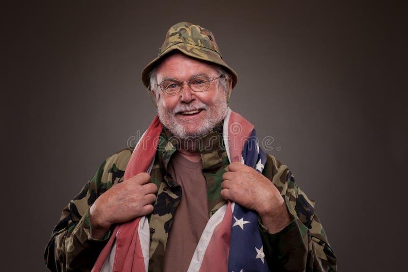 Smiling Vietnam Veteran with American flag. Happy Vietnam Veteran with American flag around his neck royalty free stock photos