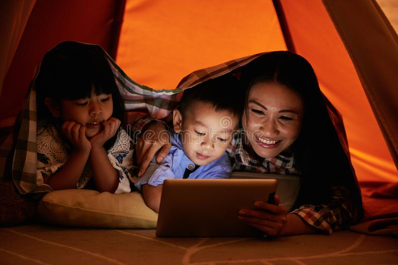 Family watching cartoons. Smiling Vietnamese women hugging her children when they are watching cartoons at night royalty free stock photography