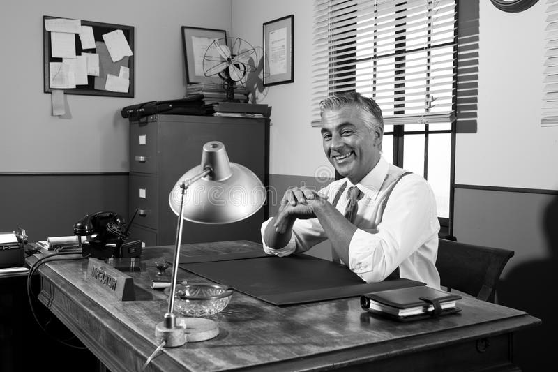 Smiling vintage director sitting at office desk. Cheerful director sitting at office desk, 1950s vintage office royalty free stock photography