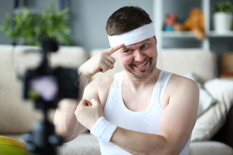 Smiling Vlogger Show Muscle on Digital Camera. Beard Man Demonstrate Muscle on Hands. Sportsman Recording Video on Professional Camcorder for Sport Vlog. Happy stock photo