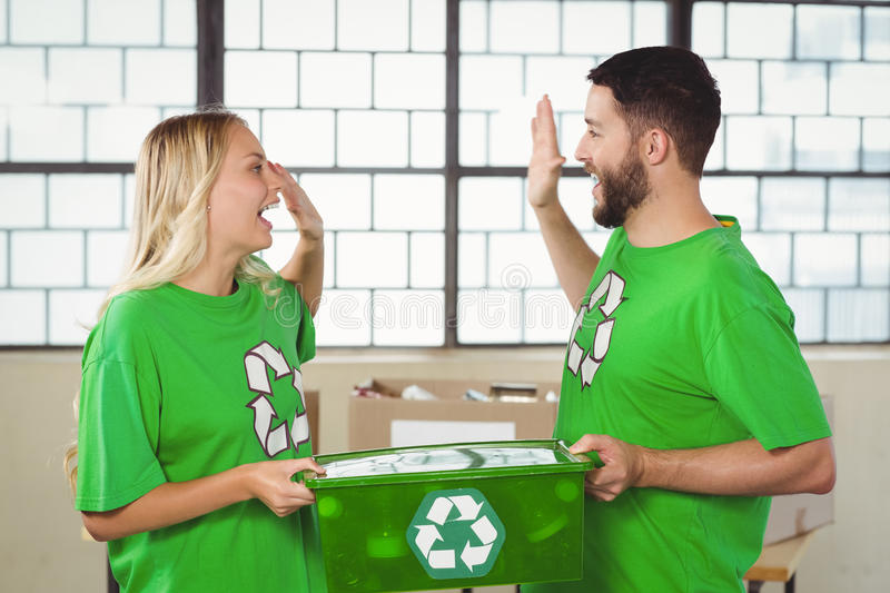 Smiling volunteer doing high five while holding container. Smiling volunteer doing high five while holding recycling container in office royalty free stock photo