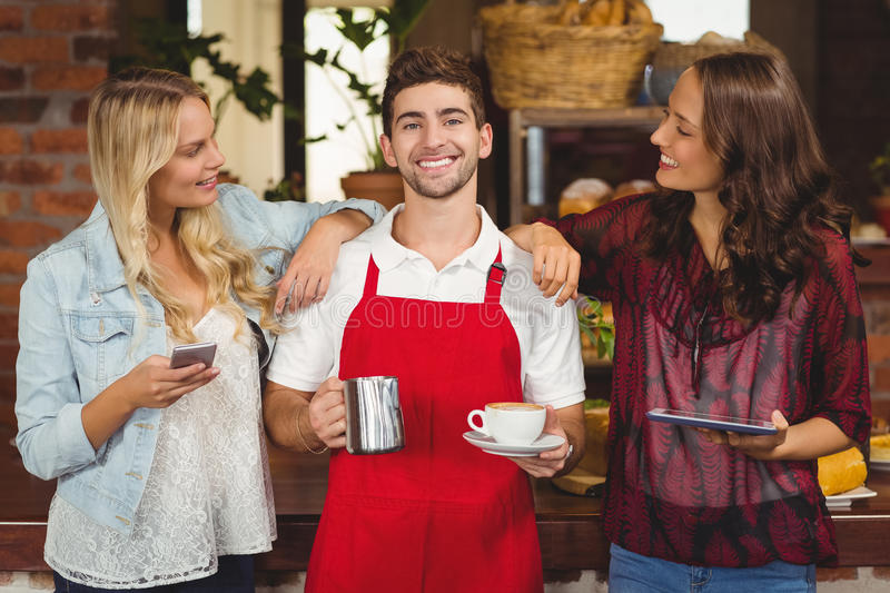 Smiling waiter and customers looking at the camera royalty free stock photo