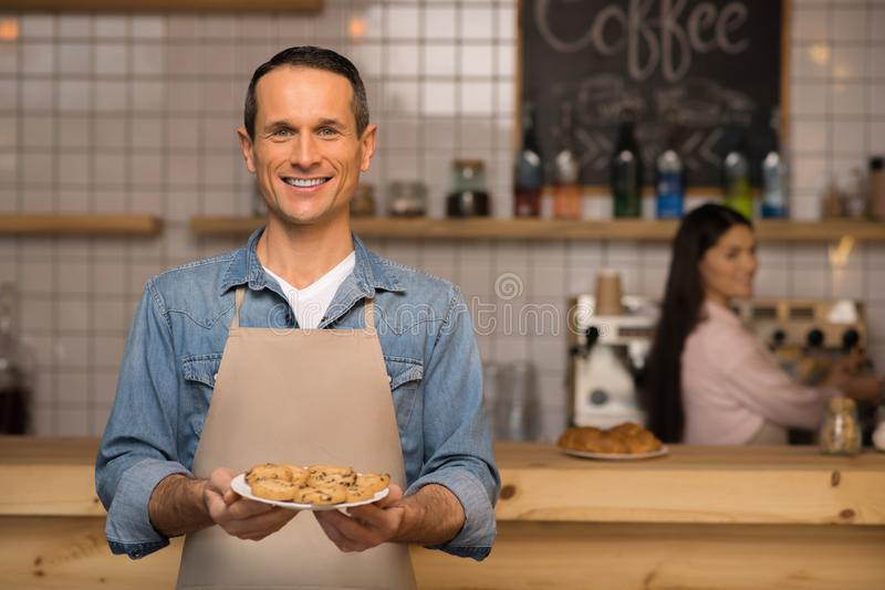 Waiter holding croissants on the plate. Smiling waiter holding croissants on the plate and looking at camera with waitress on the background royalty free stock photo