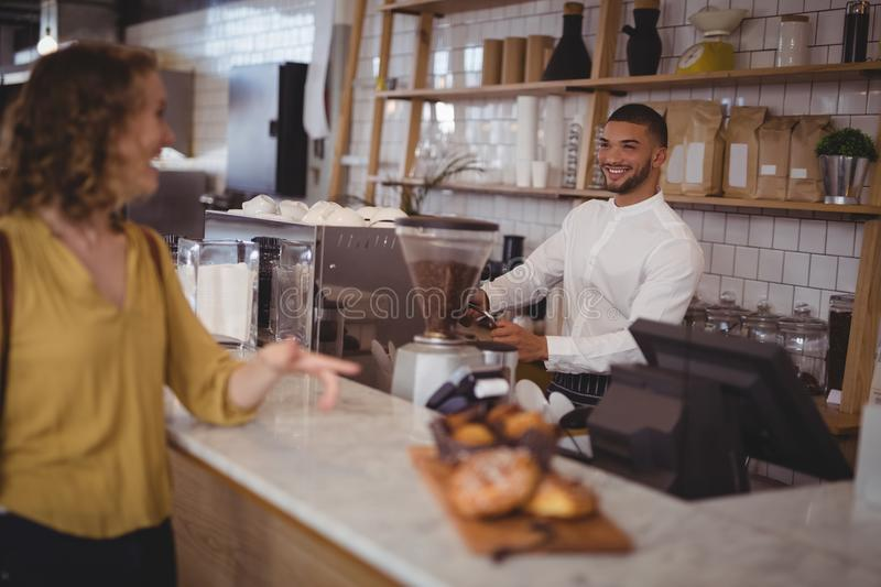 Smiling waiter looking at female customer standing at counter royalty free stock photography