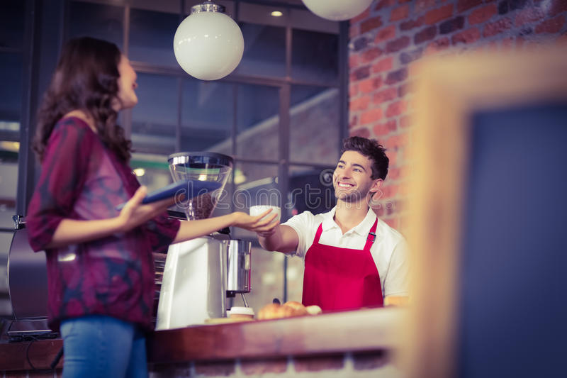 Smiling waiter serving a client stock images