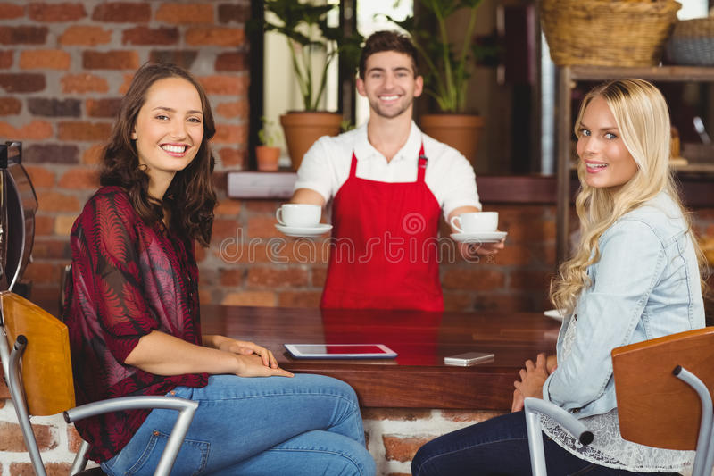 Smiling waiter serving coffees to customers royalty free stock photos