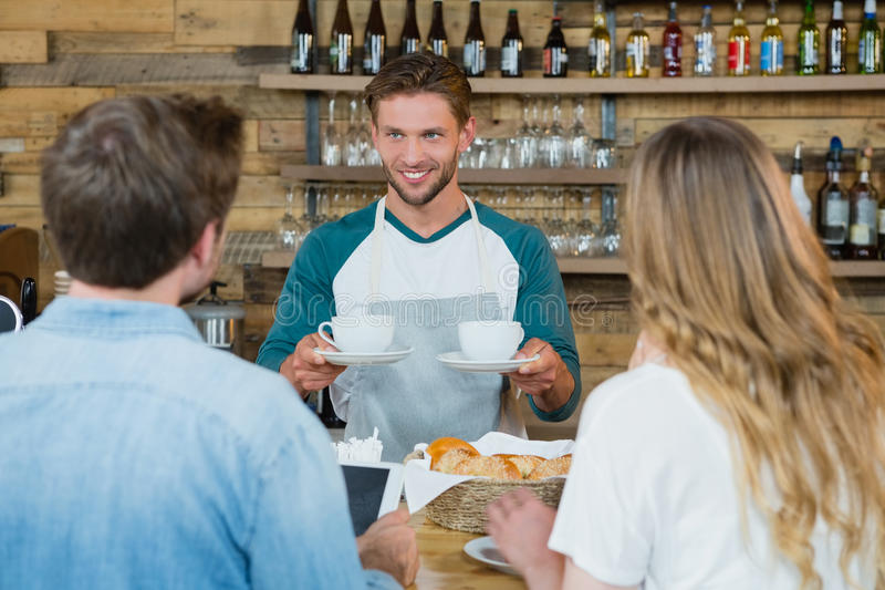Smiling waiter serving cup of coffee to customers at counter stock image