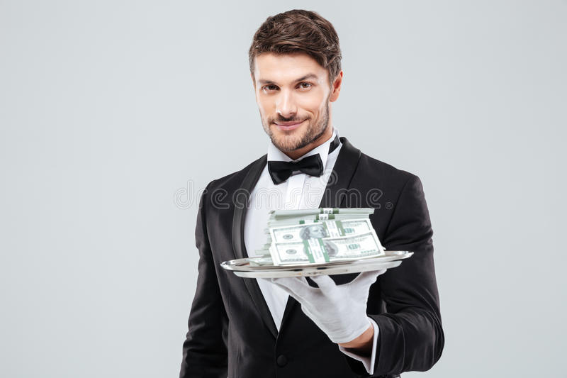 Smiling waiter in tuxedo and gloves holding tray with money stock photo