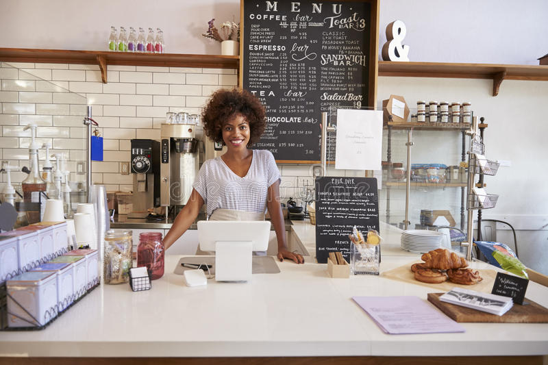 Smiling waitress behind the counter at a coffee shop stock images