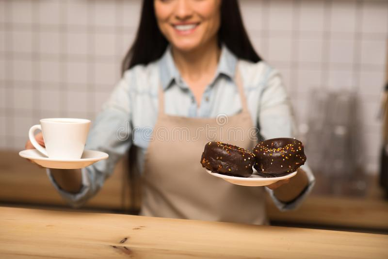 Waitress holding doughnuts cup of coffee. Smiling waitress holding chocolate doughnuts and cup of coffee, focus on the foreground stock image