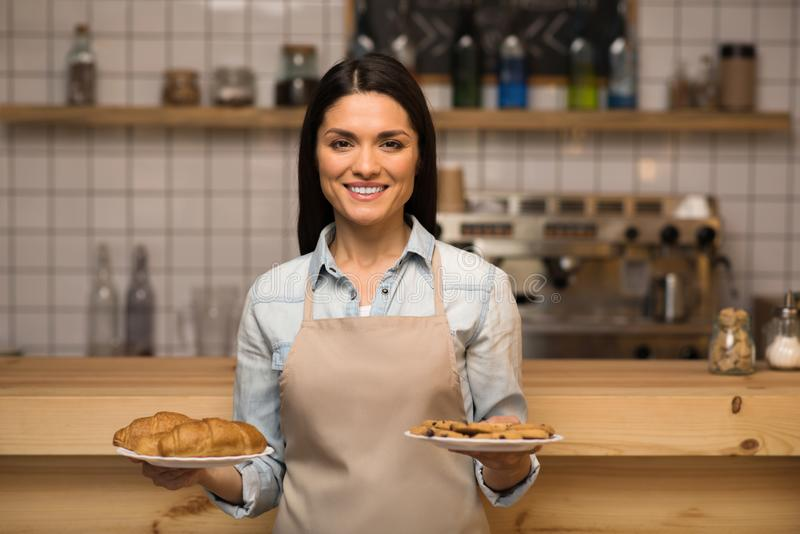 Waitress holding cookies. Smiling waitress holding cookies with croissants on the plates in the hands and looking at camera royalty free stock images
