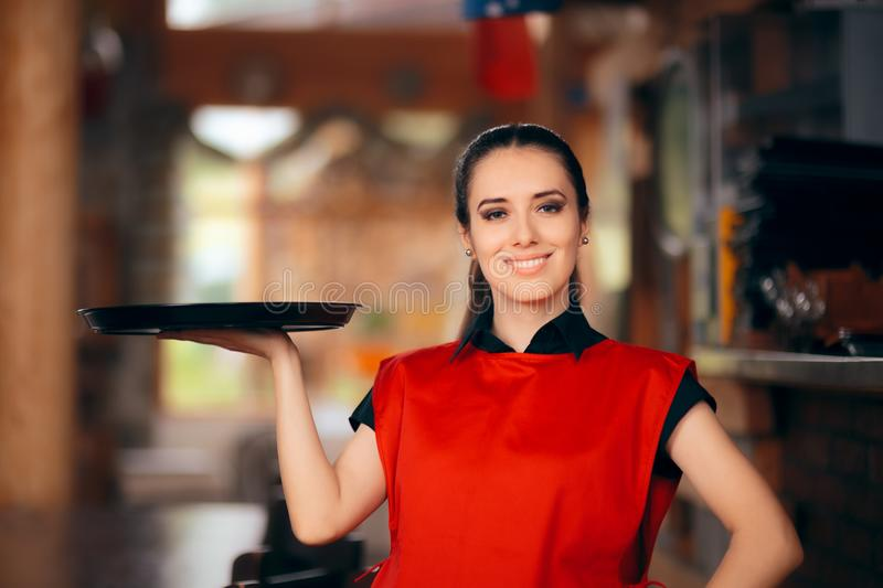 Smiling Waitress Holding Tray in a Restaurant royalty free stock photography