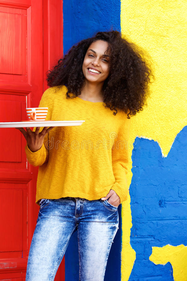 Smiling waitress holding up coffee cup on a tray stock photo