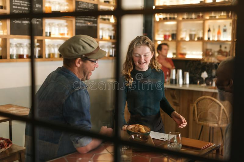 Smiling waitress serving food to a bistro customer royalty free stock photos