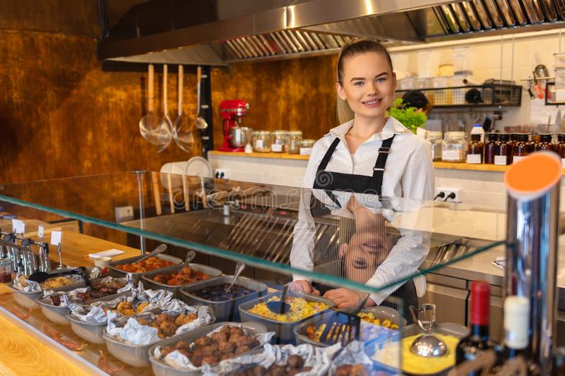 Young smiling woman waitress standing behind counter serving food in small family restaurant. Smiling waitress wearing black apron standing behind counter in stock photography