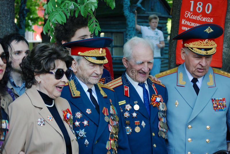 Smiling war veterans, men and woman, pose for photos. MOSCOW - MAY 09, 2016: Smiling war veterans pose for photos. Victory Day celebration in Gorky park in royalty free stock photo