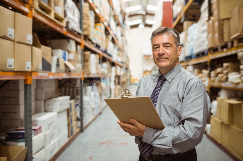 Smiling warehouse manager holding a clipboard. In a large warehouse royalty free stock images