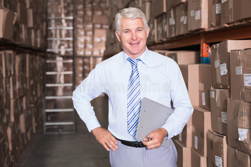Smiling warehouse manager looking at camera stock photography