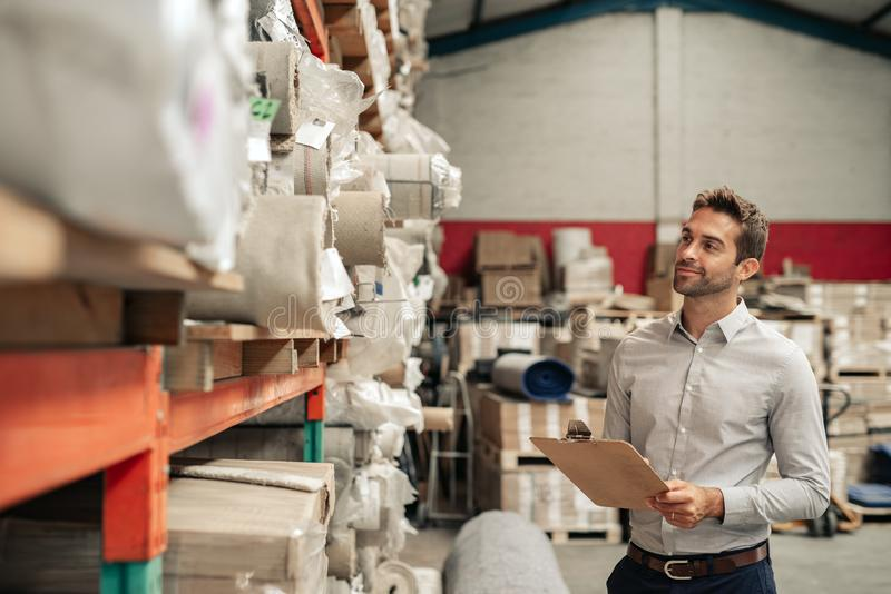 Smiling warehouse manager using a clipboard while doing inventory royalty free stock photos