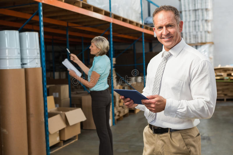 Smiling warehouse manager using tablet pc. In a large warehouse stock photo