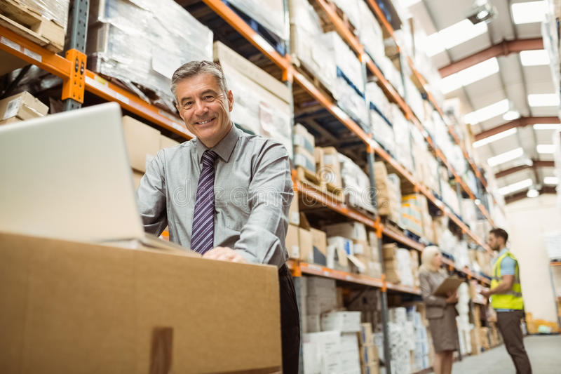 Smiling warehouse manager working on laptop royalty free stock images