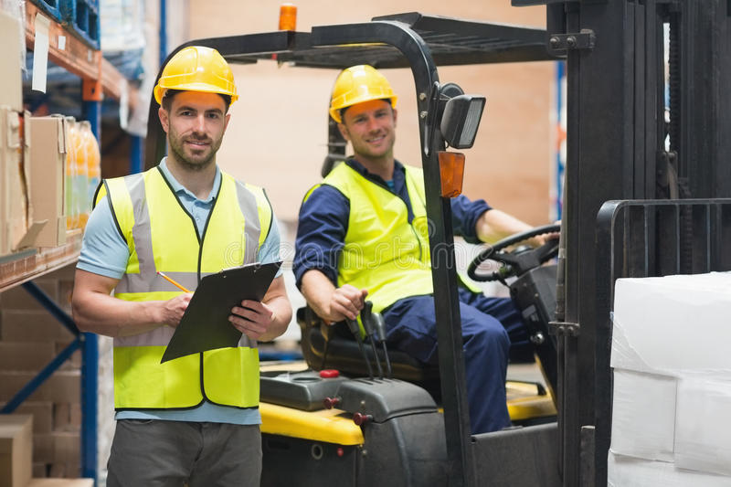 Smiling warehouse worker and forklift driver. In warehouse stock images
