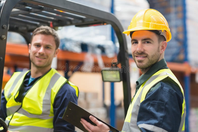 Smiling warehouse worker and forklift driver. In warehouse stock photography