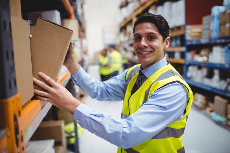Smiling warehouse worker taking package in the shelf stock photo download smiling warehouse worker taking package in the shelf stock photo image 66940568 sciox Choice Image