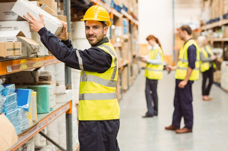 Smiling warehouse worker taking package in the shelf stock image