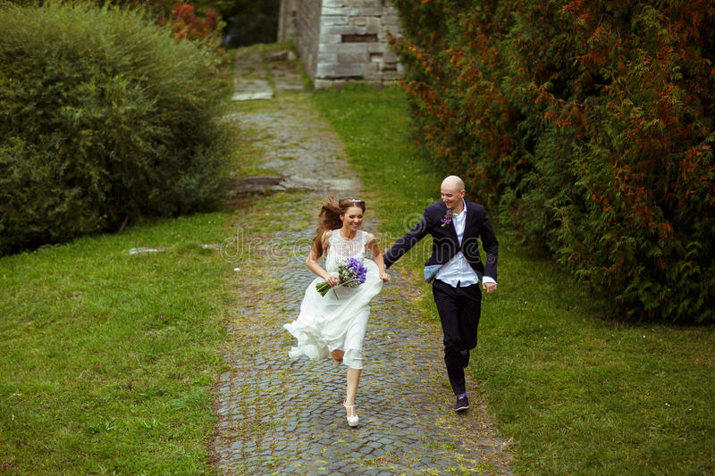 Smiling wedding couple run along the park stock images