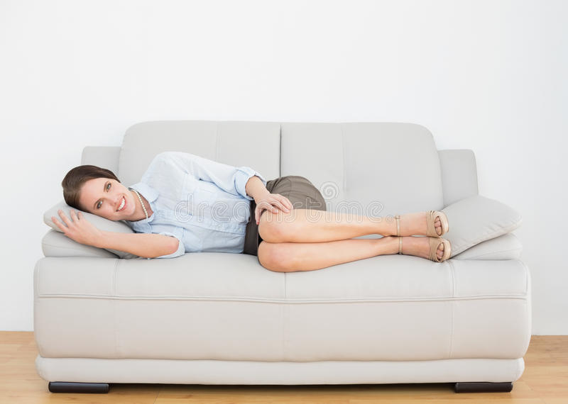 Smiling well dressed young woman relaxing on sofa royalty free stock photography